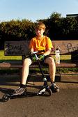 Chico guapo correteando con su scooter — Foto de Stock