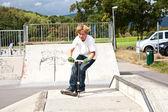 Söt pojke scooting med sin skoter — Stockfoto