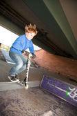 Roztomilý kluk na koloběžce s jeho skútr — Stock fotografie