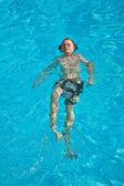 Bambino nuota in piscina e si diverte — Foto Stock
