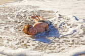 Boy lying at the beach and enjoying the ocean — Stock Photo