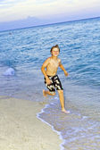 Boy is jogging at the beautiful beach — Stock Photo