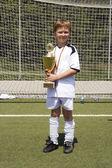 Ragazzo giovane in abito di calcio presenta fiero la coppa — Foto Stock