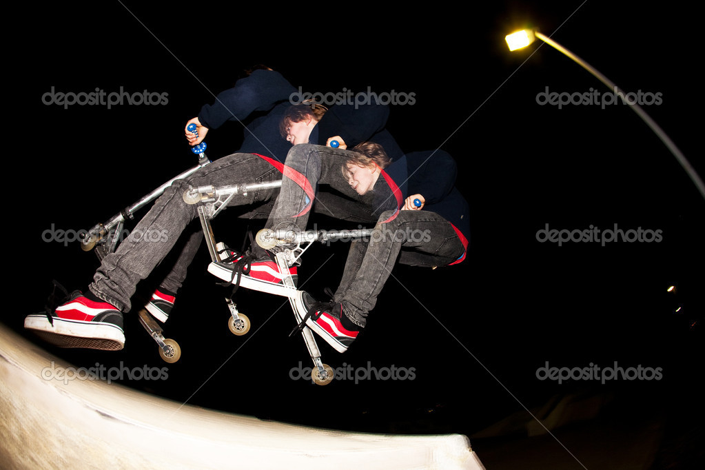 Young boy jumpy with his scooter by night with stroboscope — Stock Photo #5656554
