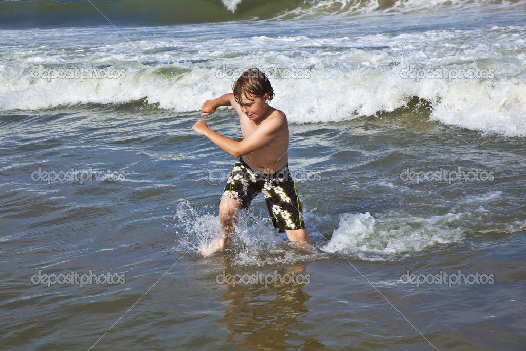 Happy young boy running through the water at the beach — Stock Photo #5656845