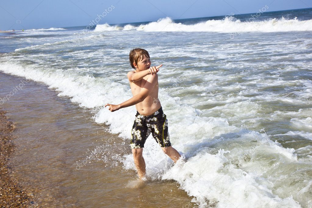 Happy young boy running through the water at the beach — Stock Photo #5656851