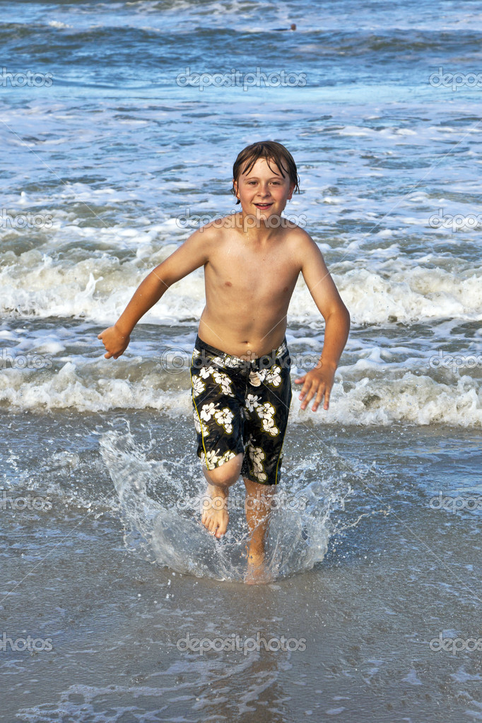 Happy young boy running through the water at the beach — Stock Photo #5656895