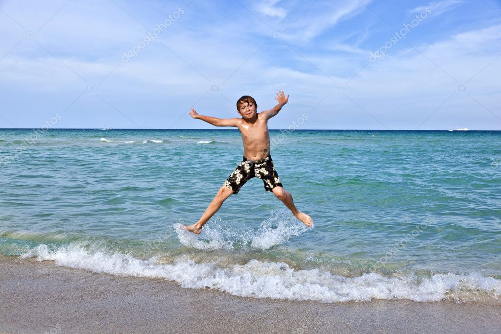 Boy jumps in the surf of the crystal clear ocean — Stock Photo #5656994