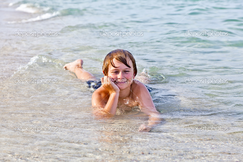 Young boy enjoys lying at the beach in the surf  Stock Photo #5656995