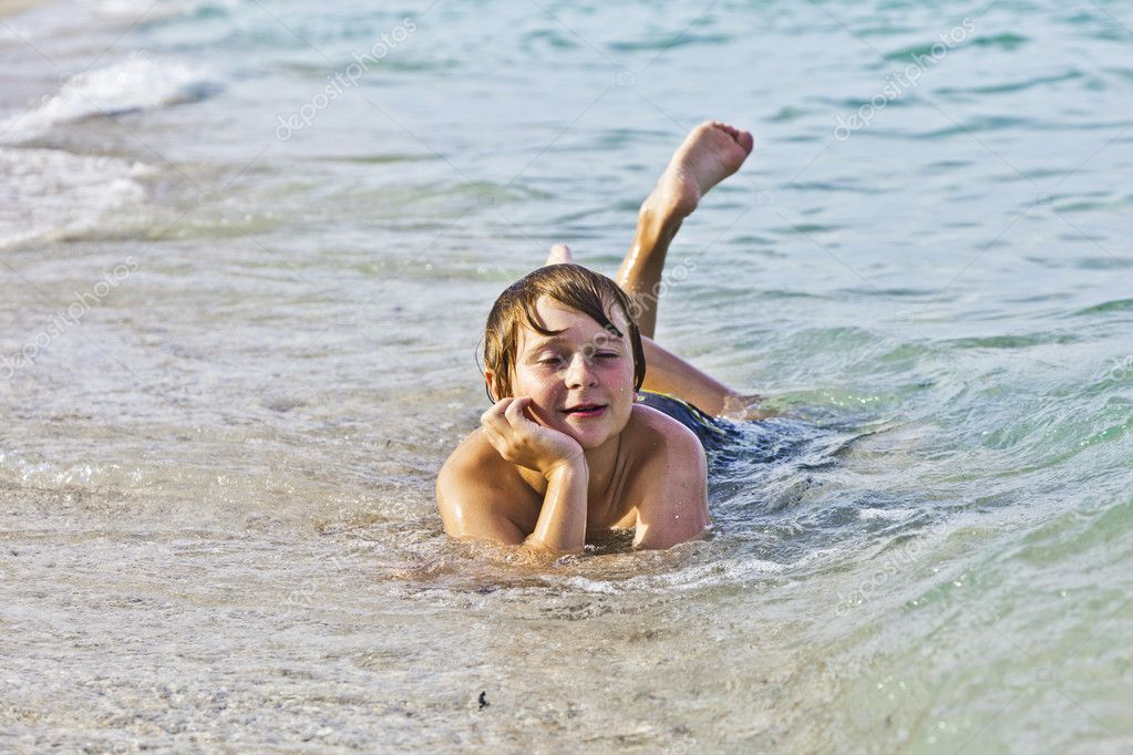 Young boy enjoys lying at the beach in the surf  Stock Photo #5656996