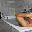 Stock Photo: Man bathing and cat strolling around the bath tube