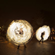 Постер, плакат: Young perform a fire spectacle at night for the audience of the Chri