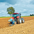 Tractor with plow on field — Stock Photo