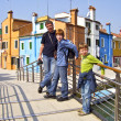 Father and sons on a bridge in colorful village of Burano — 图库照片