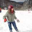 Girl and boy having fun with a snowball battle - Stock Photo