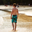 Young boy is walking along the beautiful beach in backlight — Stock Photo #5667111