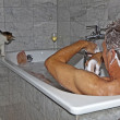 Man bathing and cat strolling around the bath tube — Stock Photo