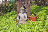 Stone buddha in front of a cherry tree — Стоковое фото