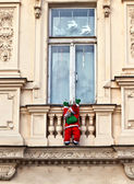 Santa claus is climbing up a facade — Stock Photo