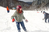 Girl and boy having fun with a snowball battle — Stock Photo
