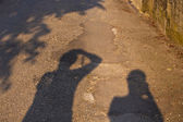 Shadow of father and son taking pictures — Stock Photo