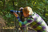 Boy taking pictures with tripot of leaves in detail — Stockfoto