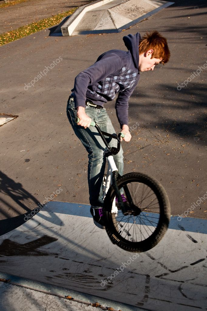 Joung red haired boy is jumping with his BMX Bike at the skate park with fun  Stock Photo #5667017