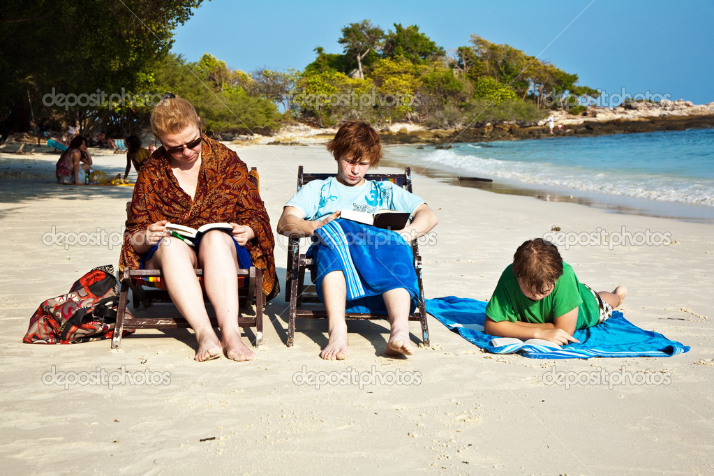 Family is enjoying the sun, relaxing, sitting at the beach and reading books — Stock Photo #5667158