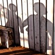 Shadow of a boy with mother at a wooden fence — Stock Photo #5671508