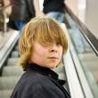 Child is smiling self confident on a stairway in a shopping mall — Stok fotoğraf