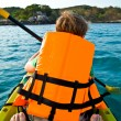 Boy paddling in a canoe at the ocean with safety west — Stock Photo