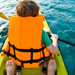 Stock Photo: Boy paddling in canoe at ocewith safety west