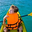 Boy paddles in a canoe at the ocean with safety west - Stock Photo