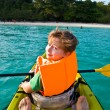 Stock Photo: Boy paddles in canoe at ocewith safety west