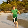Happy young boy is running along the beautiful beach — Stock Photo #5675518
