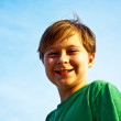 Happy smiling young boy with background blue sky irises up his a — Stock Photo #5675550