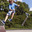 Young boy going airborne with his scooter — Stock Photo #5677034