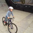 Joung boy with his mountainbike trains BMX tricks in the halfpip - Stock Photo