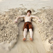 Boy is lying in a sandy bed at the beauti ful beach — Stock Photo #5678249