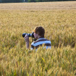Boy taking pictures with tripod of leaves in the corn field — Stock Photo #5678474