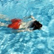Happy boy is swimming in the outdoor pool — Stock Photo #5678836