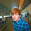 Young boy on a moving staircase inside the airport — Stock Photo #5678892