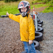 Happy boy with helmet at the kart trail - Stock Photo