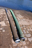 Flexible tubes for disposing liquid manure in the river — Stock Photo