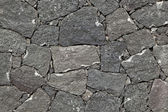 Typical wall made seamless from volcanic stone — Stock Photo
