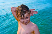Boy posing in sea with hand sign — Stock Photo