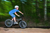 Child has fun jumping with thé bike over a ramp — Photo