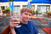 Happy smiling child toastes with pleasure with non alcoholic dri — Stock Photo
