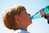 Boy is sweating and thursty and drinks mineral water — Stock Photo