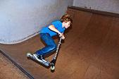 O garoto com o scooter vai no ar — Fotografia Stock